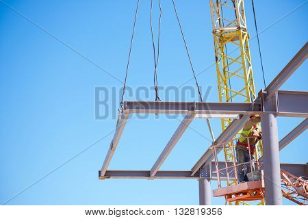 Crane works. A yellow metal construction crane used against the blue sky