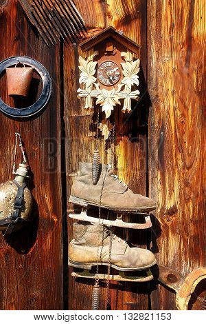 antique old style retro object assemblage on a wooden wall. rustic stile. Clock, bell, old skates and others
