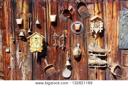 antique old style retro object assemblage on a wooden wall. rustic stile. Rake in blueberries, clock, bell, art, old skates and others