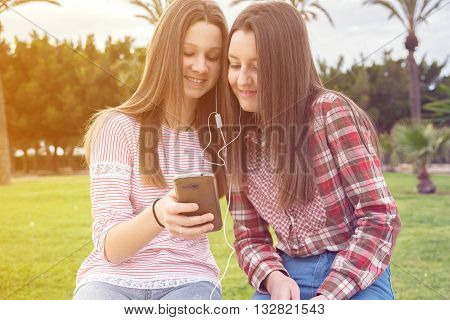 two girls were photographed on a shop listening to music in earphones in park
