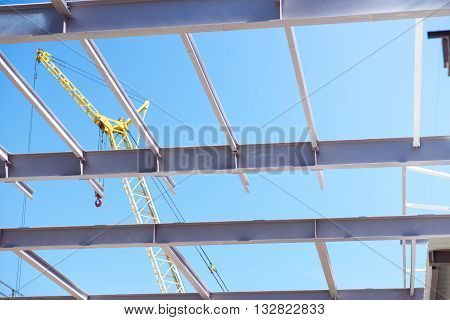 Crane in working.  A metallic construction of an undone building and a crane, picture may be used as a background