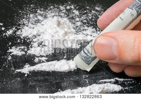 Junkie is snorting cocaine white powder with rolled banknote. Narcotics concept. poster