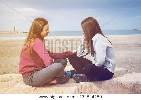 two young beautiful girls talk sitting by the sea