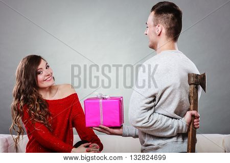 Sneaky insincere man holding axe giving gift present box to woman. Husband concealing hiding his true feelings from happy trusting wife. Untrue False intention. Relationship problems.