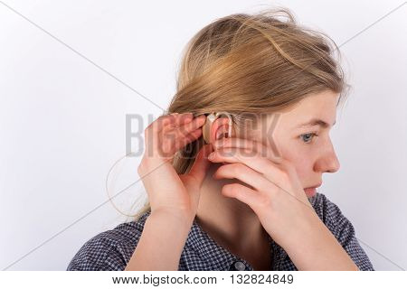 Deaf young girl setting her hearing aid.