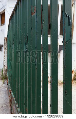 a green metal fence in deserted wharehouse