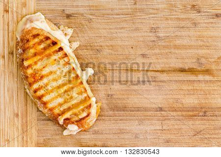 Appetizing grilled Italian panini bread cheese sandwich with melting cheese on a bamboo cutting board with copy space overhead view
