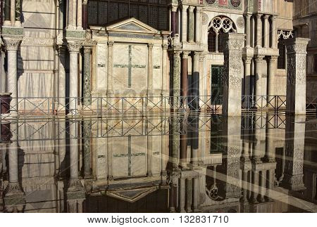 Saint Mark Basilica southern facade reflection during Venice high tide with its ancient polychrome marbles