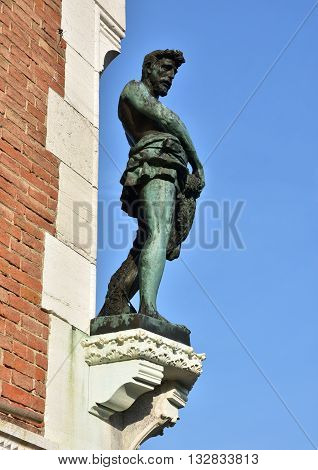 Bronze statue of Saint Peter as fisherman at the corner of Rialto Fish Market neogothic building in Venice made by artist Laurenti in 1907