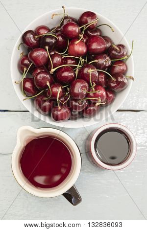 Cherries in a white bowl, stand on a blue wooden table with juice in a clay jug and cup, view from above