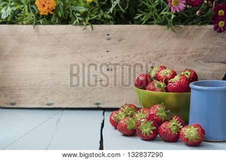 Scattered strawberry fruits in green bowl and with juice in blue clay cup on blue wooden table with wooden wall and flower in the background