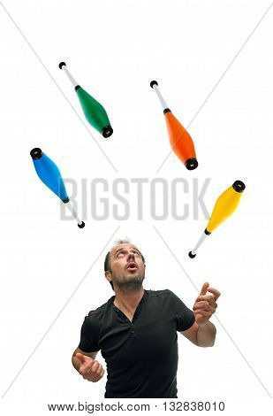 Caucasian man juggling with four colourful pins