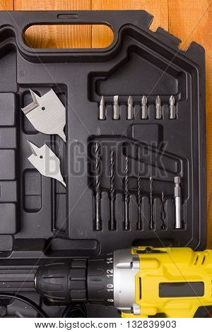 Drill and set of drill bits with screws on wooden background