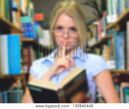 Young girl student a teacher reading a book in the library among the bookshelves silence quiet demeanor blurred
