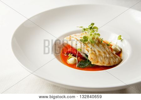 Grilled turbot, tabouli, sweet pepper sauce and summer vegetables. White dish.