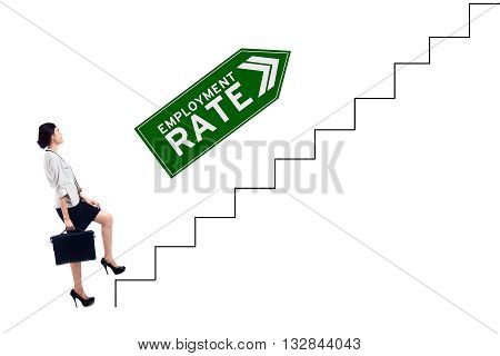 Beautiful businesswoman carrying a briefcase and walks on the staircase with employment rate text at the signpost