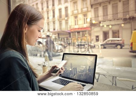 Woman at the cafe using technological devices