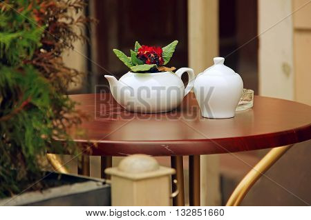 summer cafe white cup and teapot tea wooden table outdoors at the phono flowers Europe leisure tourism catering