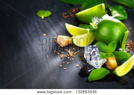 Background of Mojito cocktail ingredients on a table in summer bar, Alcohol cocktails with Rum, lime, mint, ice cubes and brown sugar closeup, Party drink. Isolated on black background,