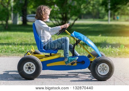 Little girl riding on the pedal karting.