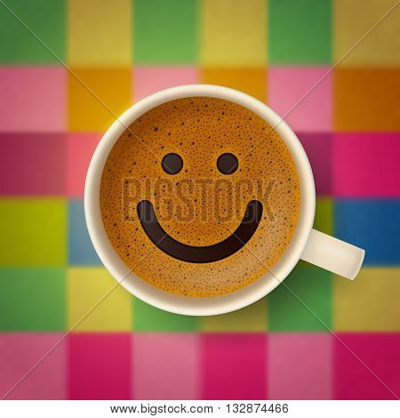 Coffee cup with funny smiling face on frothy surface, at blurred multicolor checkered textile background. Good mood and vivacity for active day