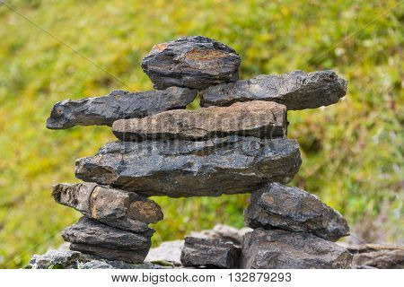 Person-shaped cairn with arms and legs with green background