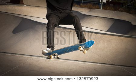 Skateboarder boy in a concrete skate park with a blue skateboard making a grind trick in the rail of a bowl.
