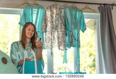 Smiling young lady in a bedroom gets dressed and ready in anticipation for her cousin's springtime wedding.  Puts some things into shopping gift bags.