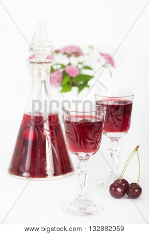 Cherry liqueur in crystal glasses with flowers in background, vertical