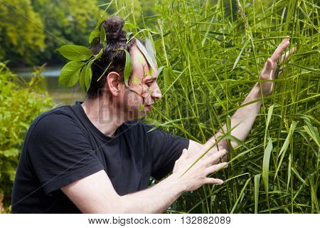 a man with leaves in face enjoying the nature