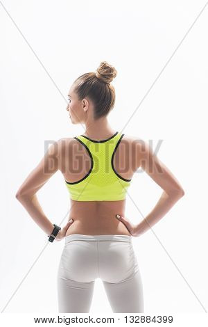 Skillful female athlete is showing her trained back. She is standing with arms akimbo. Isolated on background