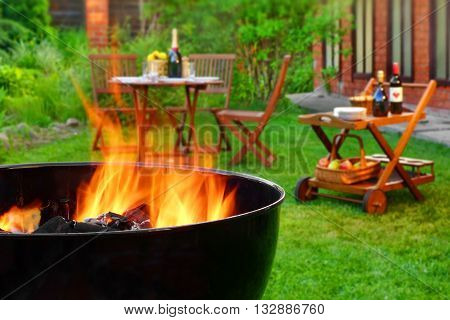 Summer Weekend BBQ Scene On The Backyard. Flaming Charcoal Grill Close Up. Outdoor Wooden Furniture On The Blurred Background. poster
