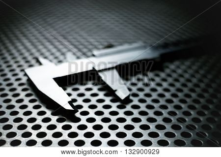 Vernier caliper on metal perforated surface with highlights