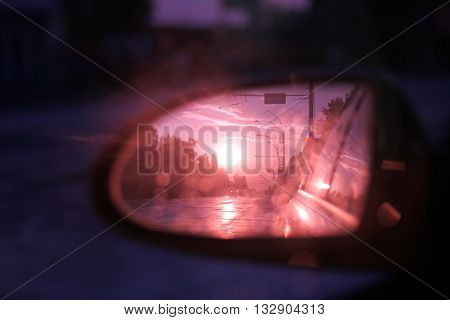 side rear-view mirror in the evening in the city during sunset