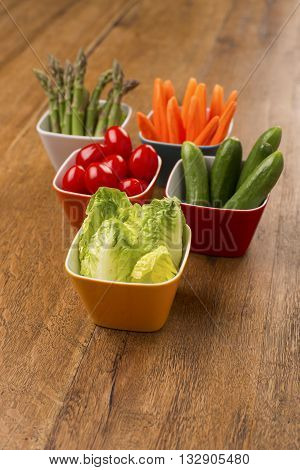 Party food, vegetables cucumbers, carrot sticks, cherry tomatoes, asparagus and baby lettuce in colourful bowls on a wooden table