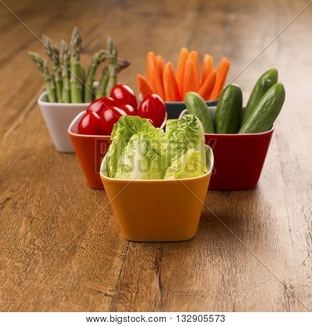 Party food, asparagus, carrots, baby lettuce hearts, plum tomatoes, cucumbers in colourful bowls