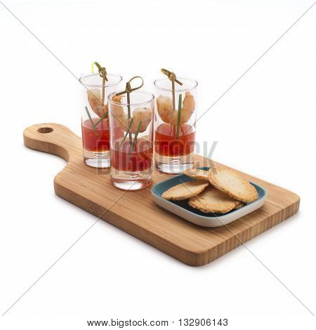 Shrimp cocktail in shot glasses with sweet and chili red sauce served on a wooden board with crackers isolated on white. Party food.