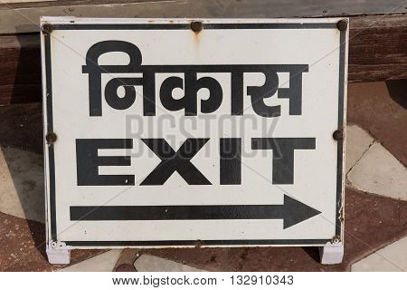 Signboard mentioning the way to exit in Taj Mahal at Agra, Delhi. The word Exit is written in both English and Hindi dialect with black color on the board.