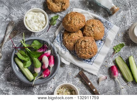 Homemade whole grain rolls cottage cheese fresh vegetables - radishes cucumbers lettuce on a grey stone background. Healthy snack in a rustic style. Top view