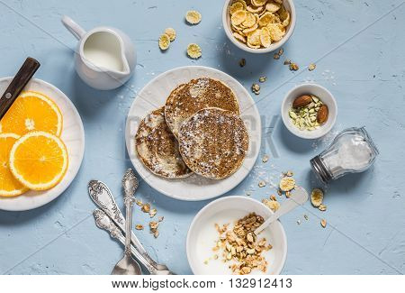 Breakfast table. Whole wheat pancakes greek yogurt with homemade granola orange slices nuts corn flakes on a blue stone background