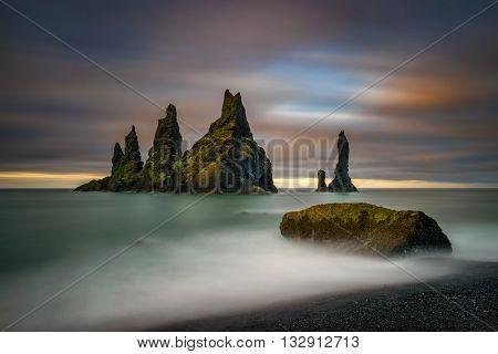 Black beach Reynisfjara and rocks at sunrise; Iceland
