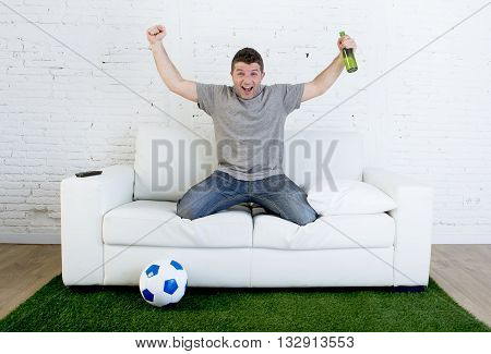 crazy football fan cheering happy watching television soccer match celebrating scoring goal excited and euphoric in sofa couch with ball and grass carpet emulating stadium pitch