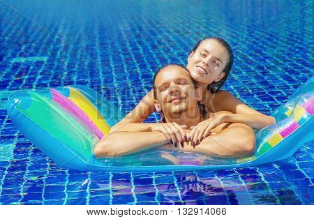 Beautiful young couple bathing in the pool on an inflatable mattress