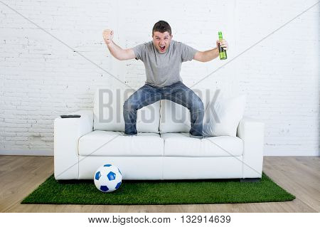 crazy football fan watching television soccer match celebrating scoring goal excited and euphoric holding beer jumping on sofa couch with ball and grass carpet emulating stadium pitch