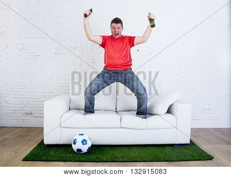crazy football fan in red team jersey cheering happy watching television soccer match celebrating scoring goal excited and euphoric in sofa couch with ball on grass carpet emulating stadium pitch