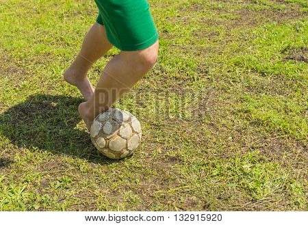 Amateur soccer on old and bad field with shabby ball and barefoot