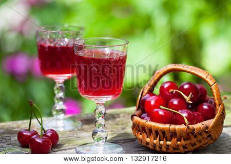 Cherry brandy and ripe berries on wooden table
