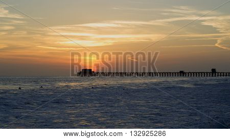 Sun setting over the Pacific ocean behind the Oceanside Pier in California