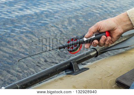 fishingfishermananglerfishing tackle in the hand of angler at fishing boat