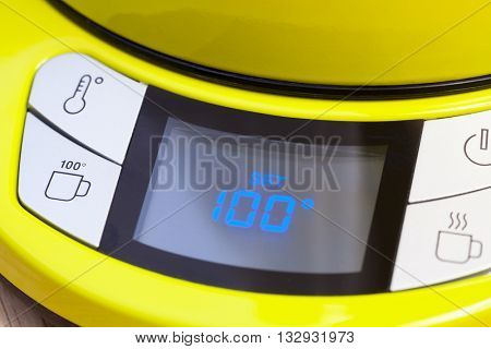 Electric tea kettle with digital thermostat control panel set to temperature of 100 degrees Celsius for brew black tea